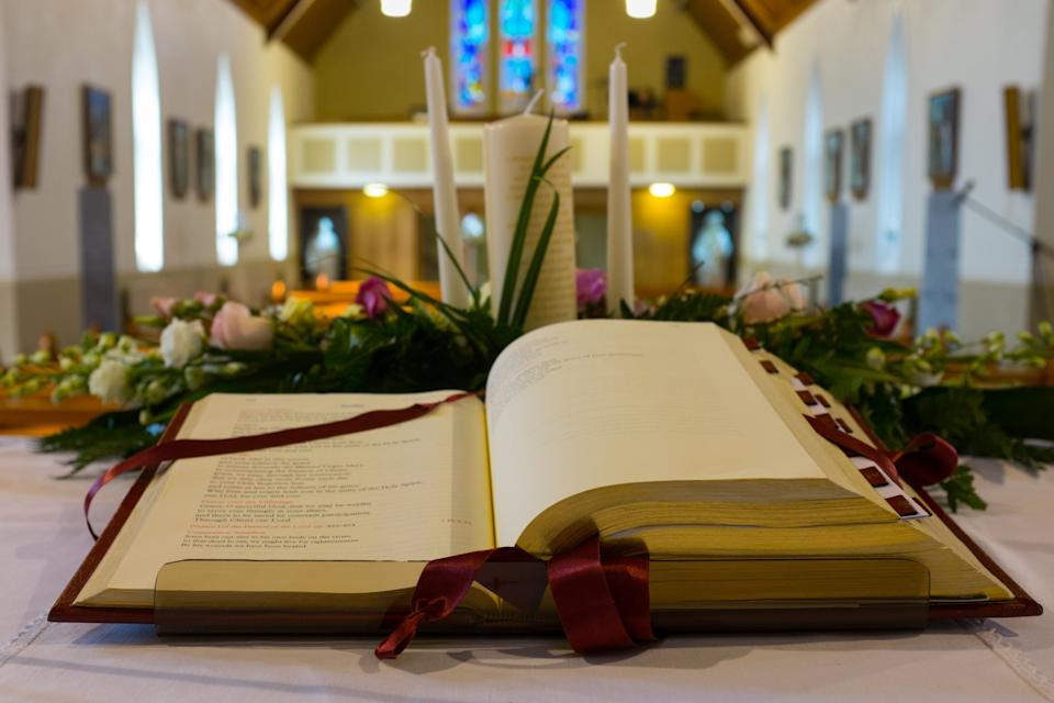 Open Bible and wedding flowers on the altar in catholic church. Shallow DOF (Photo: rihardzz via Getty Images)