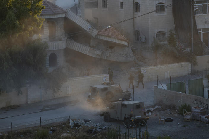 An Israeli army unit inspects the house of the Palestinian American Muntasser Shalaby following controlled explosions, in the West Bank village of Turmus Ayya, north of Ramallah, Thursday, July. 8, 2021. Israeli forces on Thursday demolished the family home of Shalaby who is accused of being involved in a deadly attack on Israelis in the West Bank in May. (AP Photo/Nasser Nasser)