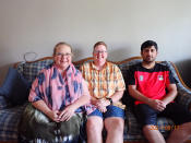 In this photo provided by Caroline Clarin, is Sheril Raymond, from left, Clarin and Ihsanullah Patan sitting together in an apartment on Tuesday, Aug. 17, 2021, in Fergus Falls, Minn. Raymond and Clarin, who worked for a U.S. Department of Agriculture in Afghanistan, helped Patan and his family arrive to the United States and get settled in Minnesota. They are part of a number of Americans trying to help Afghans fleeing their country. (Caroline Clarin via AP)