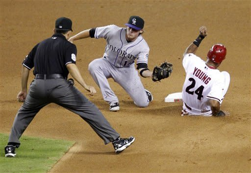 Colorado Rockies' Josh Rutledge, center, is late with the tag as Arizona Diamondbacks' Chris Young steals second base during the fourth inning of a baseball game, Tuesday, July 24, 2012, in Phoenix. (AP Photo/Matt York)