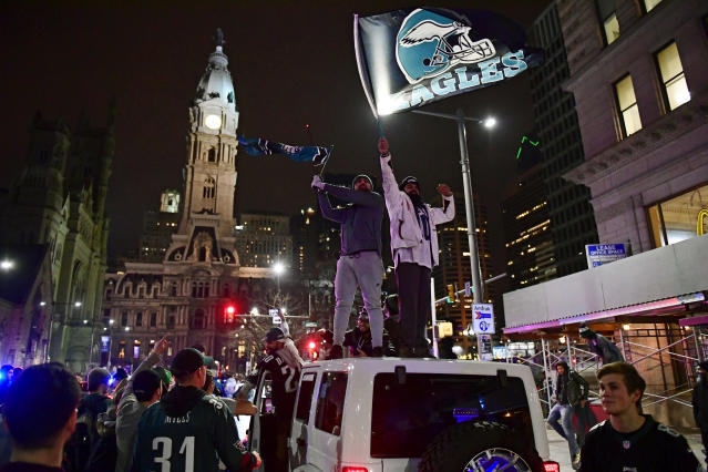 "<a class=""link rapid-noclick-resp"" href=""/nfl/teams/phi/"" data-ylk=""slk:Philadelphia Eagles"">Philadelphia Eagles</a> fans celebrate on top of cars on Broad Street. (Getty)"