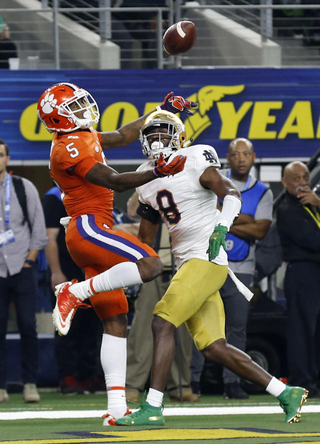 Clemson wide receiver Tee Higgins (5) reaches up to catch a ball that was tipped by Notre Dame cornerback Donte Vaughn (8) in the end zone for a touchdown late in the first half of the NCAA Cotton Bowl semi-final playoff football game, Saturday, Dec. 29, 2018, in Arlington, Texas. (AP Photo/Roger Steinman)