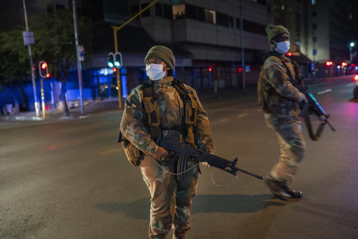 South African Defense Forces patrol downtown Johannesburg, South Africa, Friday, March 27, 2020. Police and army started patrolling moments after South Africa went into a nationwide lockdown for 21 days in an effort to mitigate the spread to the coronavirus. The new coronavirus causes mild or moderate symptoms for most people, but for some, especially older adults and people with existing health problems, it can cause more severe illness or death.(AP Photo/Jerome Delay)
