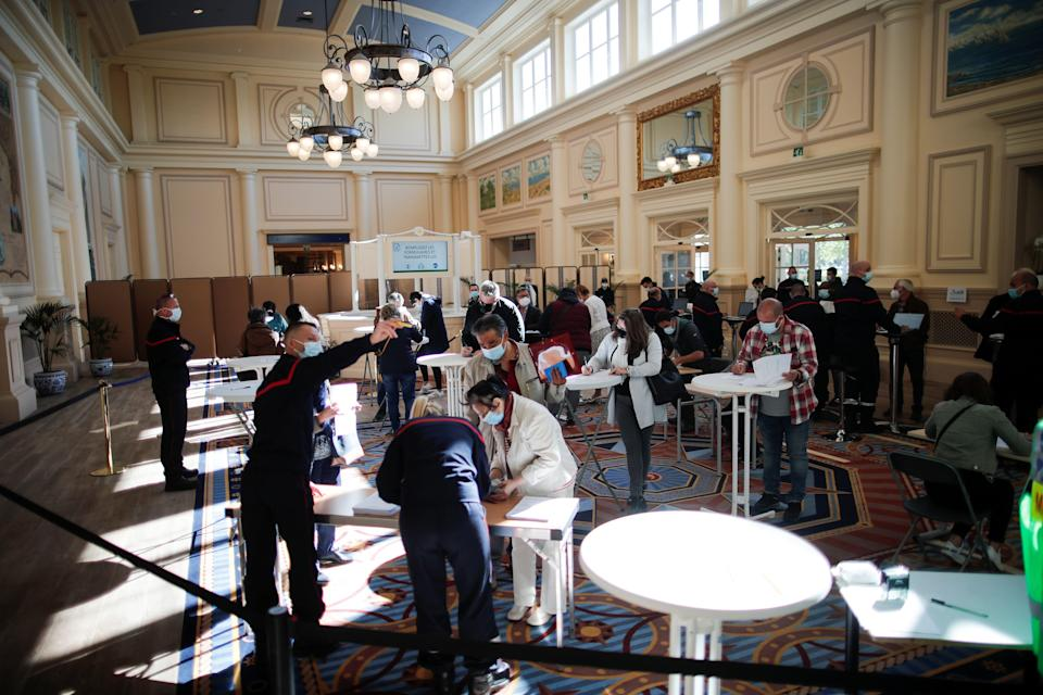 """People register to receive a dose of the """"Comirnaty"""" Pfizer BioNTech COVID-19 vaccine at the Disneyland Paris theme park vaccination center in Marne-la-Vallee, near Paris, as part of the coronavirus disease (COVID-19) vaccination campaign in France, April 24, 2021."""