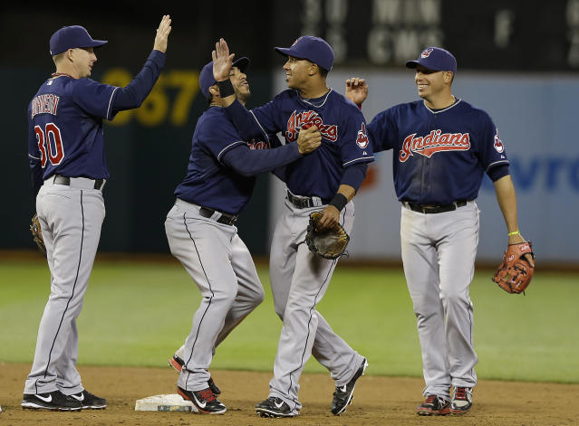Cleveland Indians' Michael Brantley, second from right, celebrates with Elliot Johnson, Mike Aviles and Asdrubal Cabrera, from left, after the last out of a baseball game against the Oakland Athletics in Oakland, Calif., Wednesday, April 2, 2014. The Indians won 6-4. (AP Photo/Jeff Chiu)