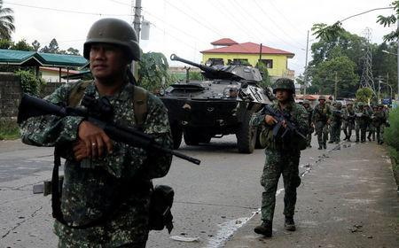Philippine Marines walk next to an armoured fighting vehicle (AFV) as they advance their positions in Marawi City, Philippines May 28, 2017. REUTERS/Erik De Castro