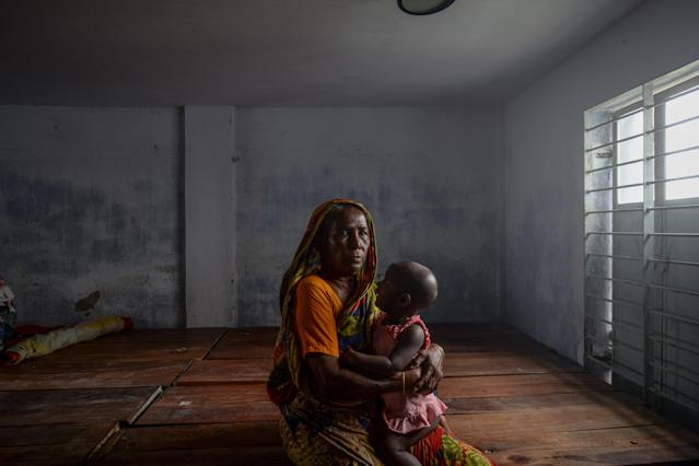 """A resident carrying a child rests in a shelter ahead of the expected landfall of cyclone Amphan in Dacope of Khulna district on May 20, 2020. - Several million people were taking shelter and praying for the best on Wednesday as the Bay of Bengal's fiercest cyclone in decades roared towards Bangladesh and eastern India, with forecasts of a potentially devastating and deadly storm surge. Authorities have scrambled to evacuate low lying areas in the path of Amphan, which is only the second """"super cyclone"""" to form in the northeastern Indian Ocean since records began. (Photo by Munir Uz zaman / AFP) (Photo by MUNIR UZ ZAMAN/AFP via Getty Images)"""