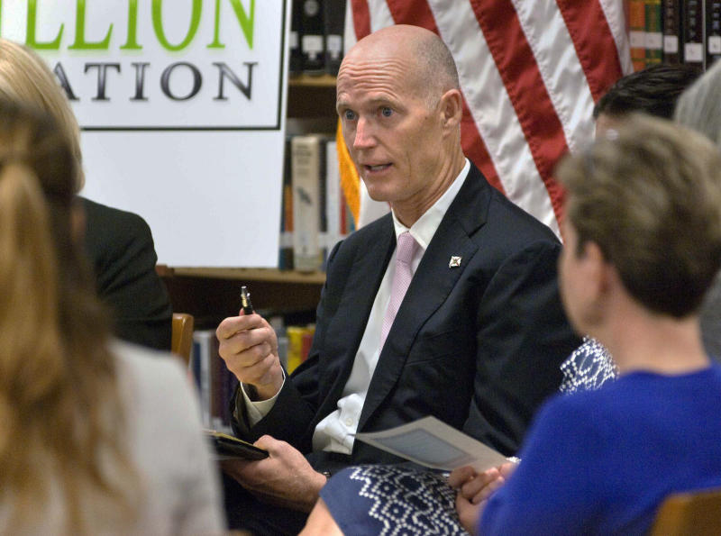 """FILE - In this Sept. 12, 2012 file photo, Florida Gov. Rick Scott talks with a group of teachers at a school in Fort Walton Beach, Fla. as part of his Education Listening tour of the state. Not long after some tea party stars took office, political analysts said, they were forced to adapt to the realities of governing and the changing political landscape, particularly in states President Obama won in last year's election. Scott, a former health care company executive who won the governorship by attacking """"Obamacare"""" and calling for deep cuts to state spending, has embraced the health care law and signed one of the largest budgets in state history, complete with pay raises for teachers. (AP Photo/Northwest Florida Daily News, Devon Ravine, File)"""