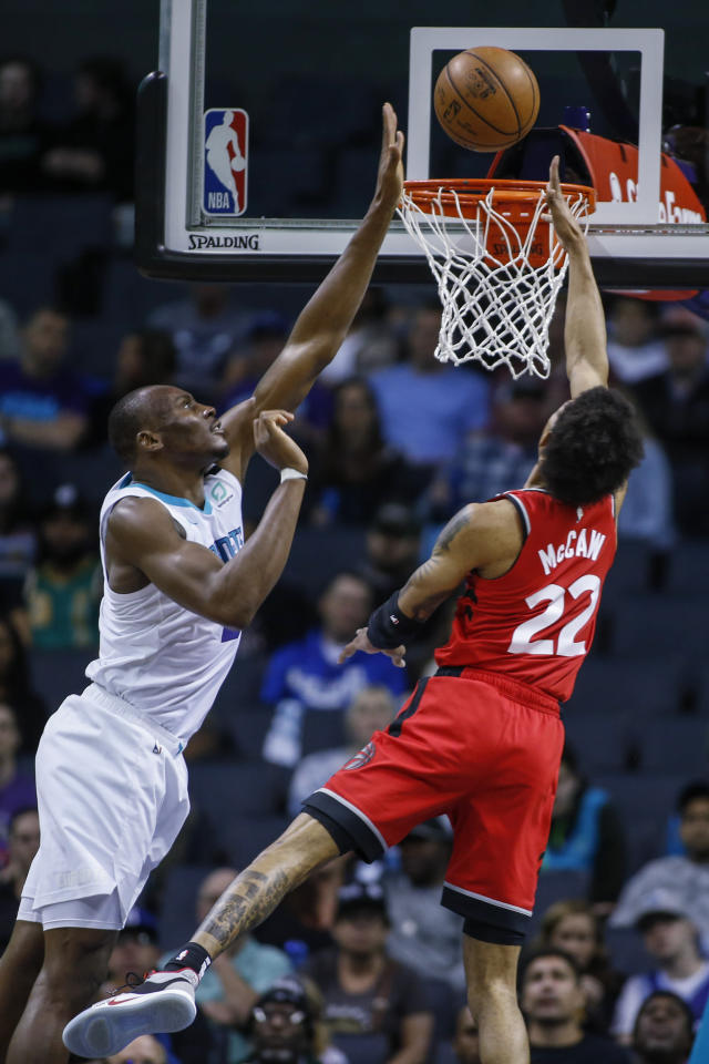 Charlotte Hornets center Bismack Biyombo, left, blocks a shot by Toronto Raptors guard Patrick McCaw during the first half of an NBA basketball game in Charlotte, N.C., Wednesday, Jan. 8, 2020. (AP Photo/Nell Redmond)