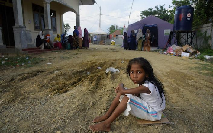 This picture taken on September 8, 2020 shows a young Rohingya girl sitting at a transit camp after nearly 300 Rohingya migrants came ashore on the beach in Lhokseumawe on the northern coast of Indonesia's Sumatra island -  RAHMAT MIRZA / AFP