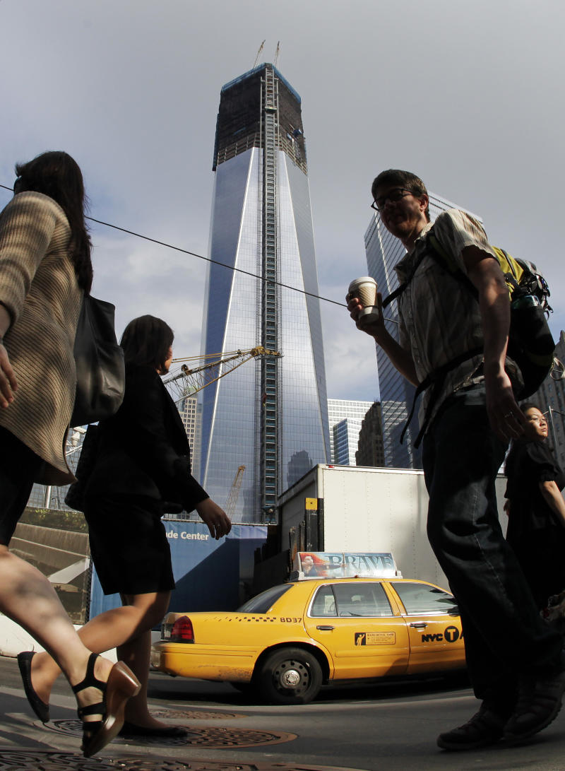 Commuters walk past the World Trade Center construction site and One World Trade Center, center, Thursday, June 14, 2012 in New York.  President Barack Obama is scheduled to visit the site later Thursday. World Trade Center PATH service will be suspended during Obama's visit and PATH trains from Newark will terminate at Grove Street in Jersey City.(AP Photo/Mark Lennihan)