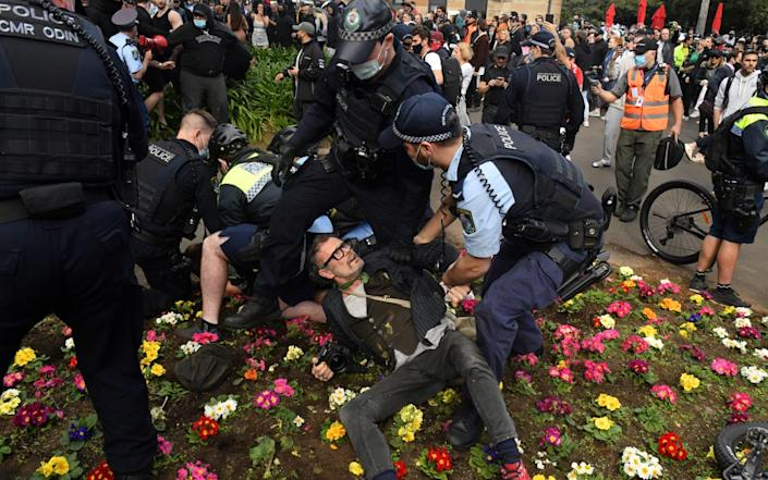 Police officers detain protesters during an anti-lockdown rally in Sydney - REUTERS