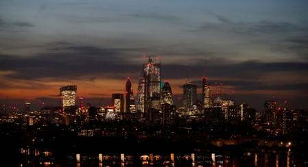 FILE PHOTO: The sun sets behind the financial district of London, Britain.