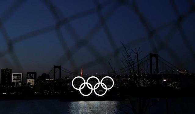 The giant Olympic rings are seen in the dusk through a steel fence at the waterfront area at Odaiba Marine Park after postponing Games due to the outbreak of coronavirus disease (COVID 19), in Tokyo