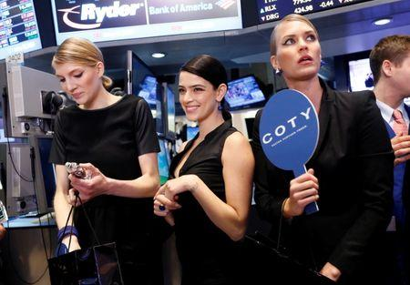 Models gather at a trading post on the floor of the New York Stock Exchange for the IPO of Coty Inc.