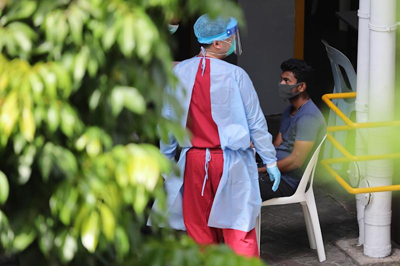 SINGAPORE - APRIL 29: A healthcare worker wearing the personal protective equipment attends to a foreign worker at a dormitory on April 29, 2020 in Singapore. Singapore is now battling to control a huge outbreak in the coronavirus (COVID-19) local transmission cases among the migrant workers. (Photo by Suhaimi Abdullah/Getty Images)