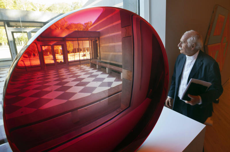 In this photo taken Oct. 13, 2011, architect Moshe Safdie looks out of a window next to a large red untitled magnifying disk sculpture by artist Fred Eversley at Crystal Bridges Museum of American Art in Bentonville, Ark.  The Crystal Bridges Museum of American Art was created using pieces acquired by Wal-Mart heir Alice Walton, who wanted to build something important in her hometown of Bentonville. The museum is scheduled to open Nov. 11. (AP Photo/Danny Johnston)
