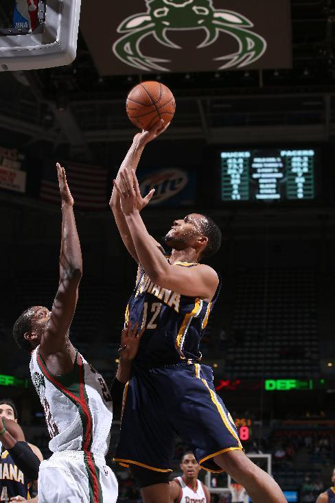 MILWAUKEE, WI - APRIL 9: Evan Turner #12 of the Indiana Pacers shoots against Khris Middleton #22 of the Milwaukee Bucks on April 9, 2014 at the BMO Harris Bradley Center in Milwaukee, Wisconsin. (Photo by Gary Dineen/NBAE via Getty Images)