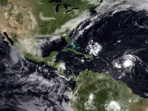 The satellite image shows tropical storms building up in the Atlantic and Pacific Oceans