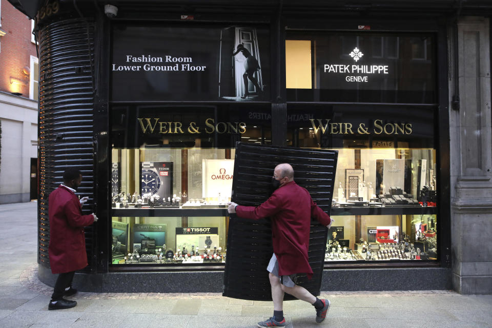 People place shutters on a jewellery shop in Dublin, Ireland, Wednesday, Oct. 21, 2020. With COVID-19 cases on the rise, the government has imposed a tough new lockdown, shutting down non-essential shops, limiting restaurants to takeout service and ordering people to stay within five kilometers (three miles) of their homes for the next six weeks. (AP Photo/Peter Morrison)