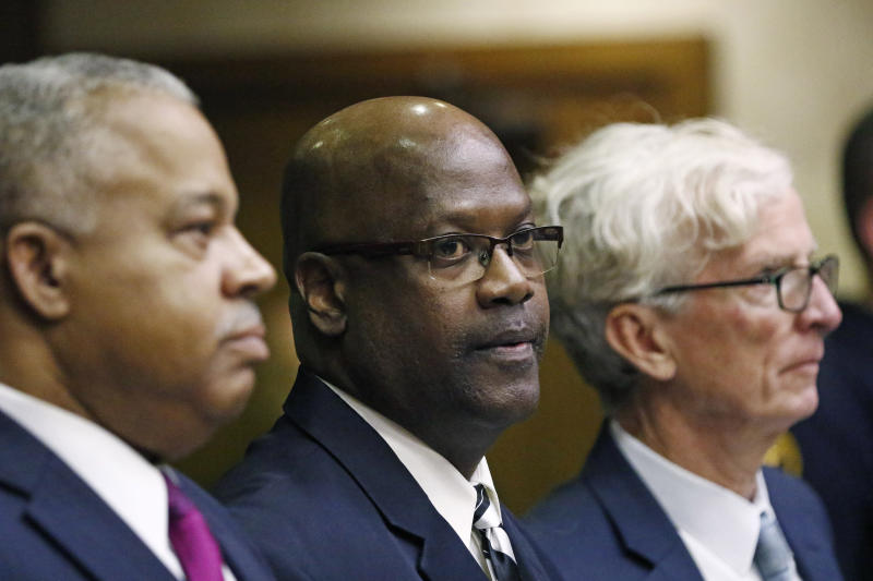 Defendant Curtis Flowers, center, stands with his attorneys Henderson Hill, left, and Rob McDuff at his bail hearing in Winona, Miss., Monday, Dec. 16, 2019. Flowers has been tried six times for murder in the 1996 shooting deaths of four people in a furniture store. Although sentenced to death during the sixth trial, the U.S. Supreme Court overturned that conviction in June, finding that prosecutors had shown a pattern of improperly excluding African American jurors in the trials. Flowers was granted bail. (AP Photo/Rogelio V. Solis)