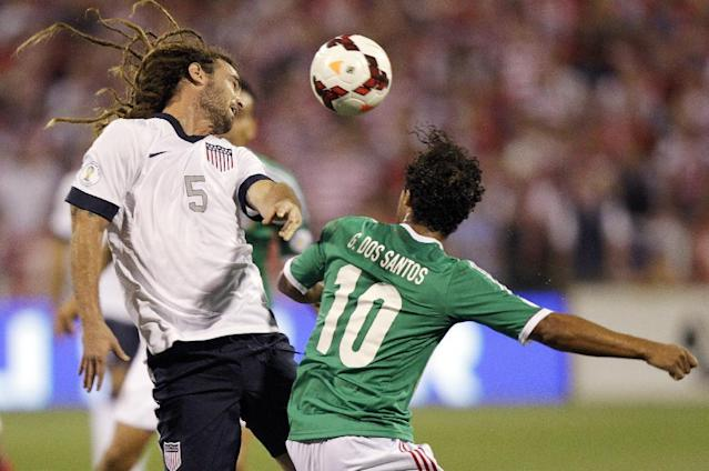 The United States' Kyle Beckerman, left, heads the ball away from Mexico's Giovani dos Santos during the first half of a World Cup qualifying soccer match Tuesday, Sept. 10, 2013, in Columbus, Ohio. (AP Photo/Jay LaPrete)