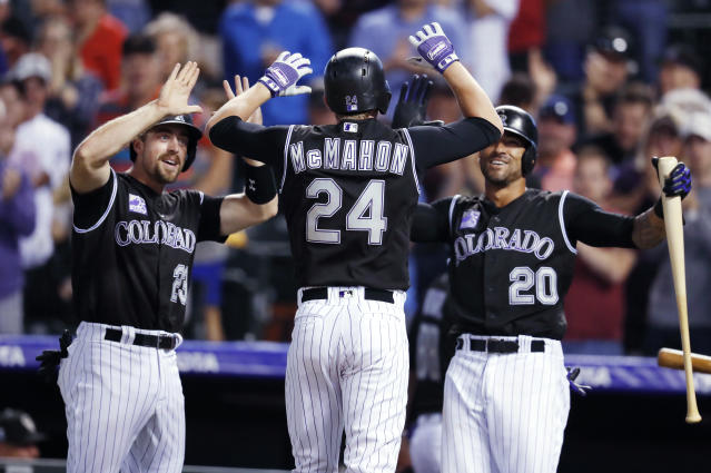 Colorado Rockies pinch-hitter Ryan McMahon, center, is congratulated by Tom Murphy, left, and Ian Desmond as McMahon crosses home plate after hitting a three-run home run off New York Mets relief pitcher Robert Gsellman during the fifth inning of a baseball game Wednesday, June 20, 2018, in Denver. (AP Photo/David Zalubowski)