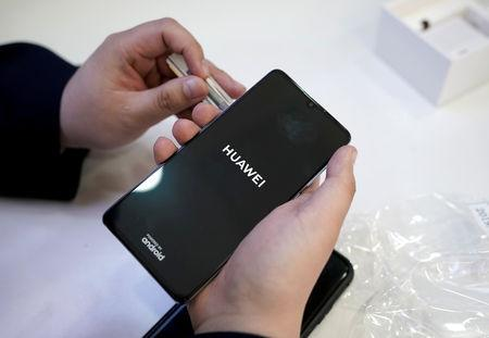 FILE PHOTO: A salesman turns on a new Huawei P30 smartphone for a customer in Beijing