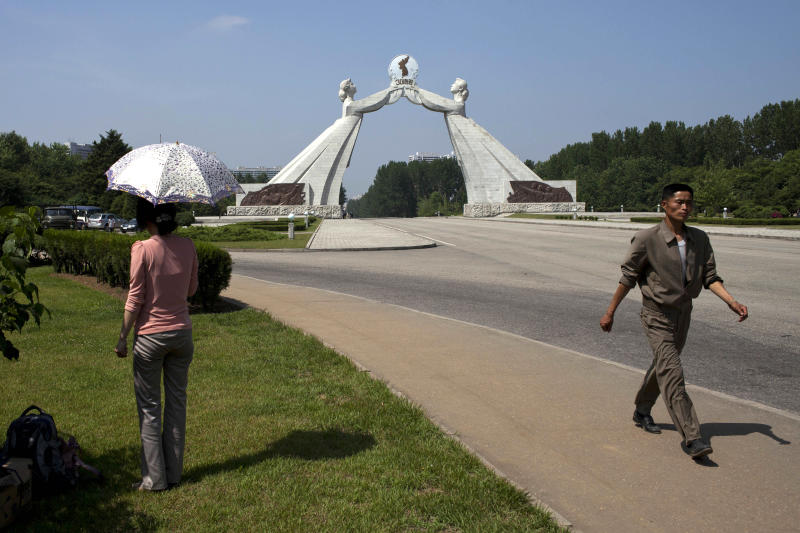 A woman rests under an umbrella while a man walks past her near a statue known as the Monument to the Three Charters for National Reunification, which symbolizes the hope for eventual reunification of the two Koreas, in Pyongyang, North Korea, Saturday, June 15, 2013. In past years, the monument built over the road leading to South Korea has been the site of celebrations marking a joint reconciliation declaration signed by the two Koreas on June 15, 2000. This year's events were canceled after high-level talks between the Seoul and Pyongyang governments, the first in six years, were called off earlier in the week. (AP Photo/Alexander Yuan)