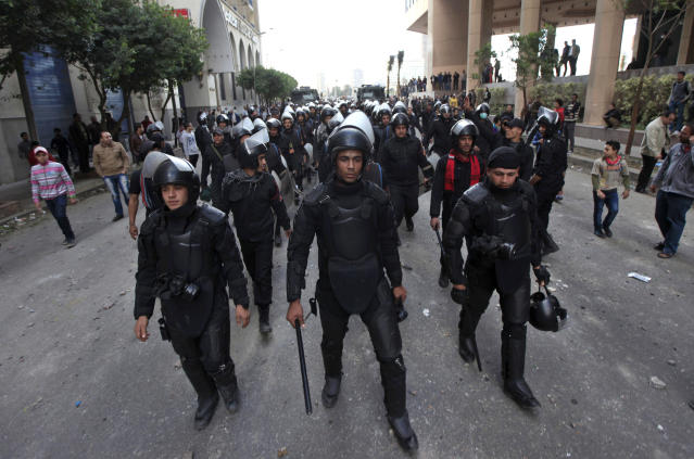 Egyptian riot police march during clashes with protesters, not seen, near Tahrir Square in Cairo, Egypt,Wednesday, Jan. 30, 2013. Egypt's liberal opposition leader called for a broad national dialogue with the Islamist government, all political factions and the powerful military on Wednesday, aimed at stopping the country's eruption of political violence that has left scores dead in the past week. (AP Photo/Khalil Hamra)