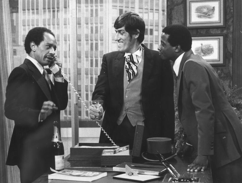 """FILE - In this 1977 file photo provided by CBS, from left, Sherman Hemsley, Paul Benedict, and Damon Evans star in an episode of """"The Jeffersons."""" Hemsley, the actor who made the irascible, bigoted George Jefferson of """"The Jeffersons"""" one of television's most memorable characters and a symbol for urban upward mobility, was found dead Tuesday, July 24, 2012 at his El Paso, Texas home. He was 74. (AP Photo/CBS, File)"""