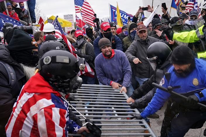 Rioters try to break through a police barrier Wednesday at the Capitol in Washington.