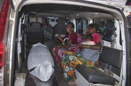 Unidentified women wail beside the body of a woman, who underwent sterilisation surgery at a government mass sterilisation camp, inside an ambulance outside Chhattisgarh Institute of Medical Sciences (CIMS) hospital in Bilaspur, in the eastern Indian state of Chhattisgarh, November 12, 2014. REUTERS/Stringer
