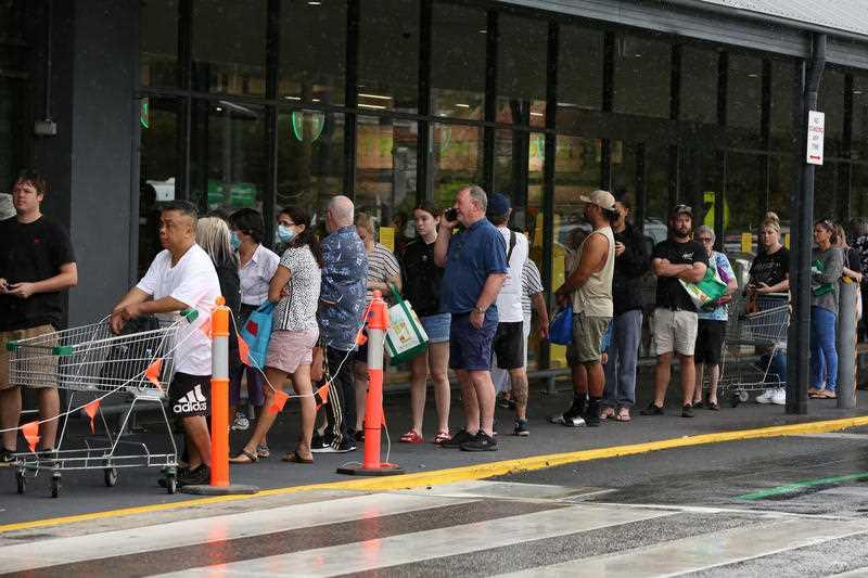 A queue is seen forming outside Woolworths at Chermside Marketplace in Brisbane.