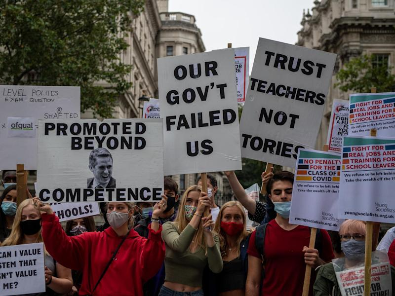 Students, teachers and parents hold placards and wear face masks as they protest against downgraded results: Chris J Ratcliffe/Getty Images