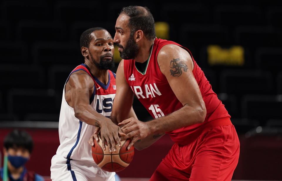 United States' Kevin Durant (7), left, tries to steal the ball from Iran's Hamed Haddadi (15) during men's basketball preliminary round game at the 2020 Summer Olympics, Wednesday, July 28, 2021, in Saitama, Japan. (AP Photo/Charlie Neibergall)