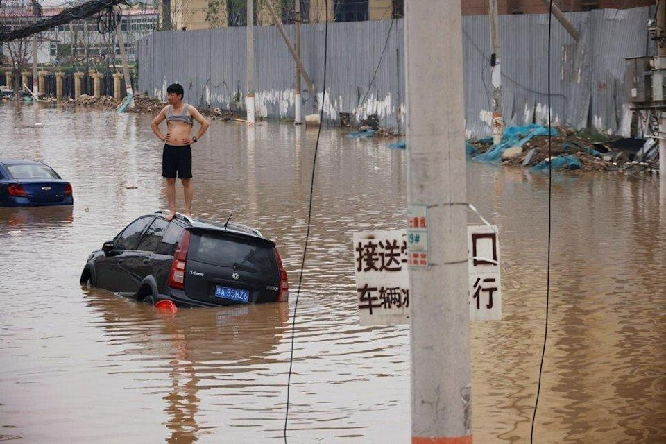 A man stands on a stranded vehicle on a flooded road following heavy rainfall in Zhengzhou, Henan province, China July 22, 2021. Photo: Reuters