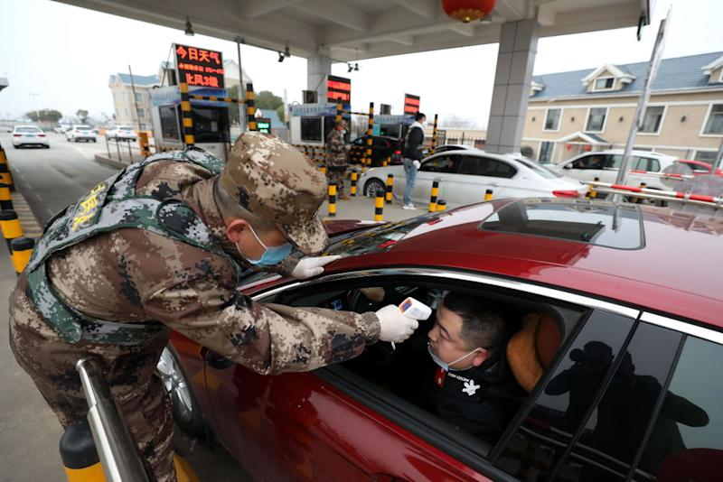 A militia member checks the body temperature of a driver on a vehicle at an expressway toll gate in Wuhan. Source: Getty