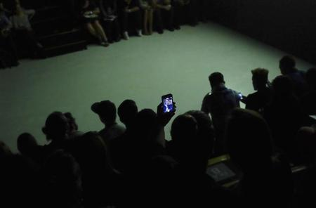 """Visitors take a """"selfie"""" with a mobile phone near the runway during Sao Paulo Fashion Week"""