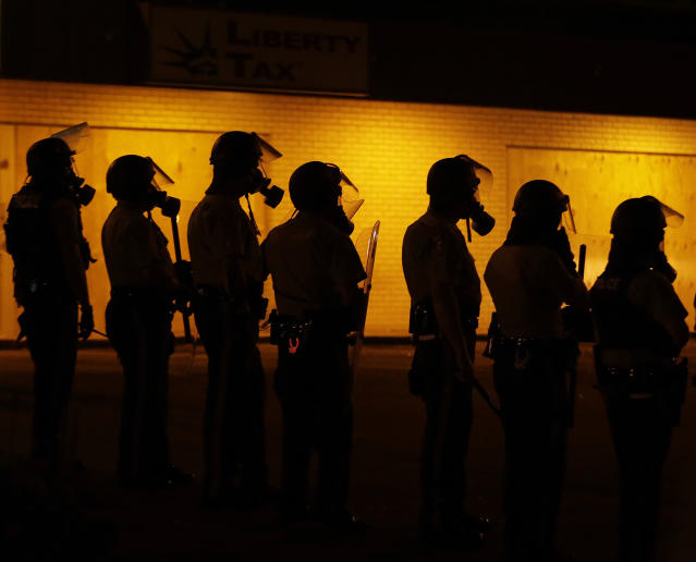 <p>Police wait to advance after tear gas was used to disperse a crowd Sunday, Aug. 17, 2014, druing a protest for Michael Brown, who was killed by a police officer last Saturday in Ferguson, Mo. As night fell Sunday in Ferguson, another peaceful protest quickly deteriorated after marchers pushed toward one end of a street. Police attempted to push them back by firing tear gas and shouting over a bullhorn that the protest was no longer peaceful. (AP Photo/Charlie Riedel) </p>