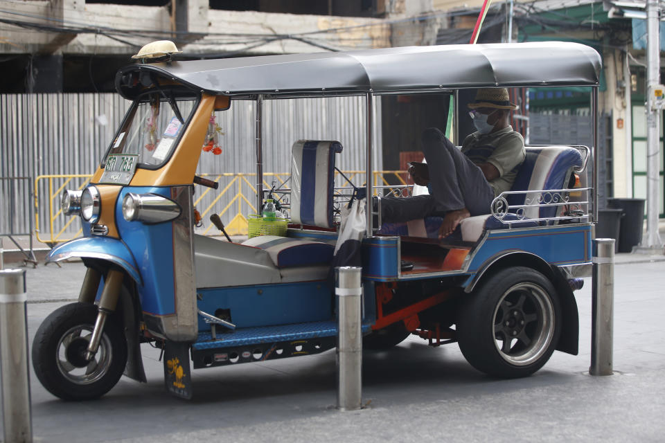 A tuk tuk driver wearing a face mask to help curb the spread of the coronavirus waits for customers in Khao San road, a popular hangout for Thais and tourists in Bangkok, Thailand, Monday, April 26, 2021. Cinemas, parks and gyms were among venues closed in Bangkok as Thailand sees its worst surge of the pandemic. A shortage of hospital beds, along with a failure to secure adequate coronavirus vaccine supplies, have pushed the government into imposing the new restrictions. (AP Photo/Anuthep Cheysakron)