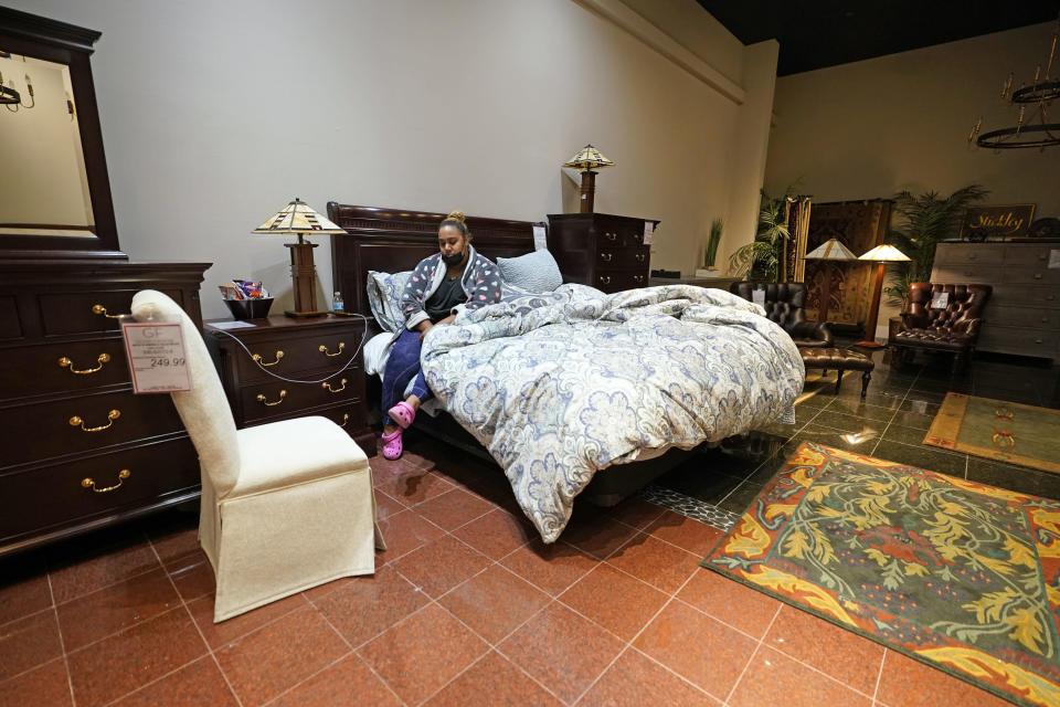 Taylor Brown wakes up after spending the night inside a Gallery Furniture store which opened as a shelter for those in need of food, water and heat Wednesday, Feb. 17, 2021, in Houston. Millions in Texas still had no power after a historic snowfall and single-digit temperatures created a surge of demand for electricity to warm up homes unaccustomed to such extreme lows, buckling the state's power grid and causing widespread blackouts. (AP Photo/David J. Phillip)