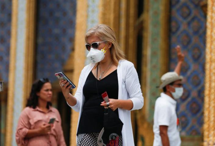 Tourists wear protective face masks at Emerald Buddha temple, which is usually full of tourists, amid fear of coronavirus in Bangkok