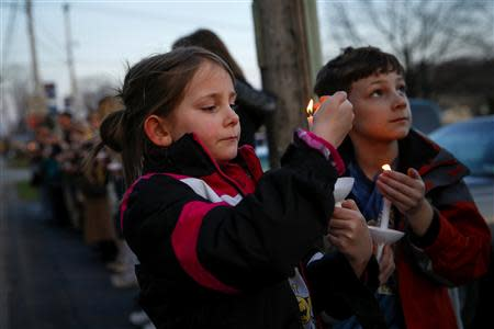 Ashlin (L) and Jude Burkhart, from Murrysville, hold candles during a prayer vigil for victims of the Franklin Regional High School stabbing rampage, at Calvary Lutheran Church in Murrysville, Pennsylvania April 9, 2014. REUTERS/Shannon Stapleton