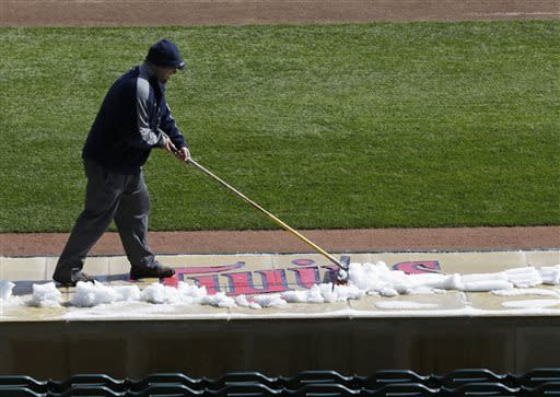 A Minnesota Twins grounds crew worker removes snow from the dugout roof prior to the start of the first game of a day/night baseball double header against the Miami Marlins Tuesday, April 23, 2013 in Minneapolis, Minn. Monday's game was postponed due to snow. (AP Photo/Jim Mone)