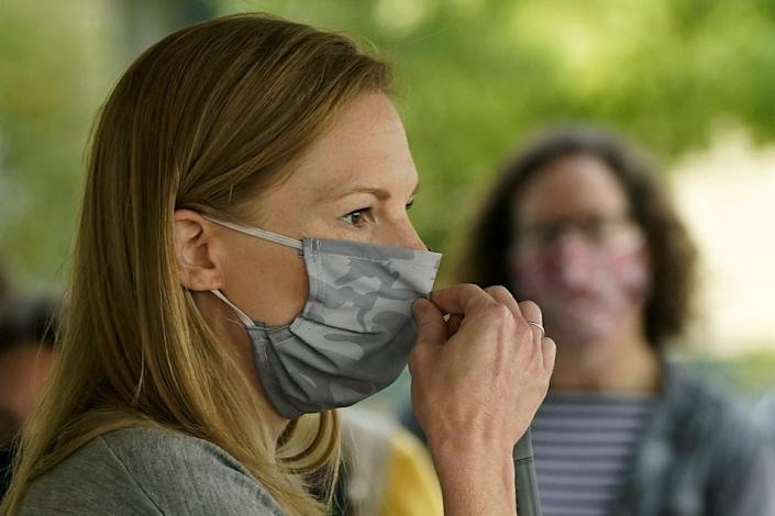 In this Sept. 19, 2020, file photo, Missouri State Auditor and Democratic gubernatorial candidate Nicole Galloway adjusts her face mask as she addresses the crowd during a campaign stop Saturday, Sept. 19, 2020, in Kansas City, Mo. (AP Photo/Charlie Riedel)