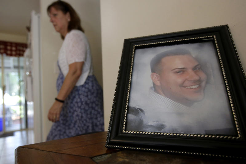 FILE - In this Tuesday, June 19, 2018 file photo Cheryl Juaire walks past a photo of her son, Corey Merrill, at her home in Marlborough, Mass. Victims of opioid addiction weren't in the room when big decisions were hammered out in OxyContin maker Purdue Pharma's proposal to settle claims over its role in the U.S. opioid crisis. Cheryl Juaire lost her 23-year-old son to a heroin overdose after he became addicted to prescription painkillers. (AP Photo/Steven Senne, File)