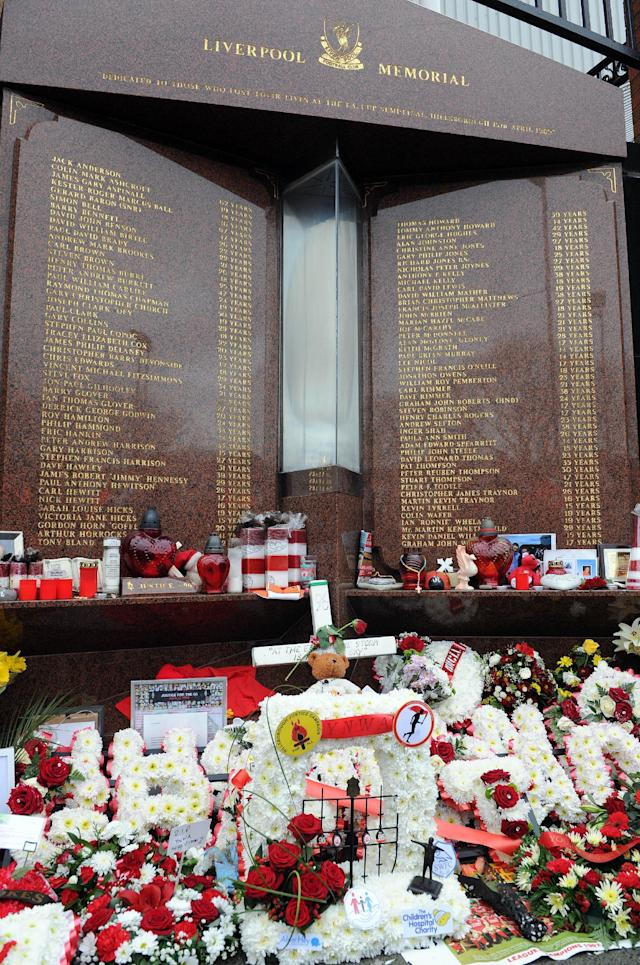 Tributes are laid at the memorial of the Hillsborough disaster outside Anfield before the English Premier League soccer match between Liverpool and Manchester City at Anfield in Liverpool, England, Sunday, April 13, 2014. (AP Photo/Clint Hughes)