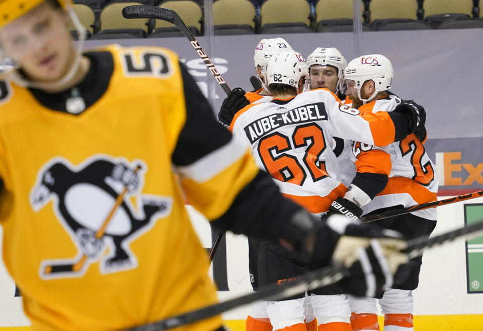 Pittsburgh Penguins' Jake Guentzel, left, skates away as Philadelphia Flyers' Claude Giroux, right, celebrates with teammates after scoring during the second period of an NHL hockey game Thursday, March 4, 2021, in Pittsburgh. (AP Photo/Keith Srakocic)