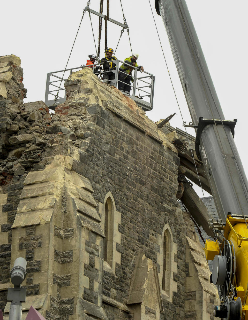 FILE - In this Feb. 25, 2011, file photo, recovery operation workers are lowered by crane onto the top of the earthquake damaged Christ Church Cathedral in Christchurch, New Zealand. The Christ Church Cathedral was arguably New Zealand's most iconic building before much of it crumbled during an earthquake 10 years ago. The years of debate that followed over whether the ruins should be rebuilt or demolished came to symbolize the paralysis that has sometimes afflicted the broader rebuild of Christchurch. But as the city on Monday, Feb. 22, 2021 marks one decade since the quake struck, killing 185 people and upending countless more lives, there are finally signs of progress on the cathedral. It's being rebuilt to look much like the original that was finished in 1904, only with modern-day improvements to make it warmer and safer. (AP Photo/Rob Griffith, File)